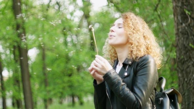 stockvideo's en b-roll-footage met schattig meisje spelen met blow ball. outdoor fashion portret van jonge romantische krullend blonde met paardebloem in het park. lente, zomer. - blond curly hair