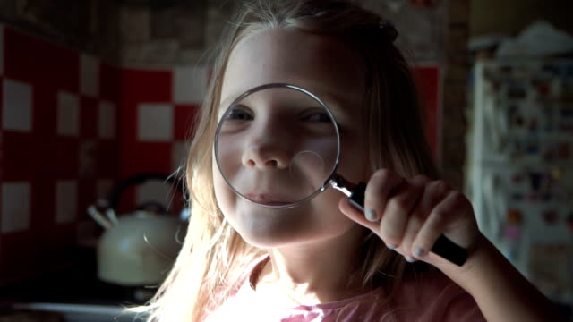 Cute girl playing with loupe video