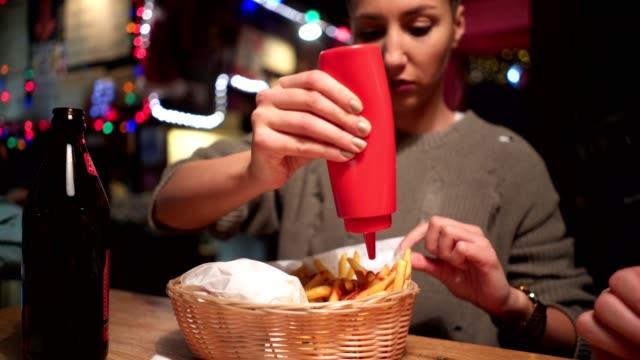ragazza carina mettendo ketchup sopra patatine fritte al pub - ketchup video stock e b–roll