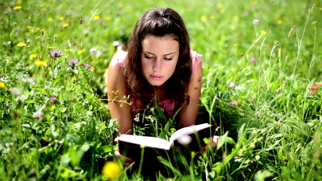 hd: cute girl reading book on a meadow - ligga på mage bildbanksvideor och videomaterial från bakom kulisserna