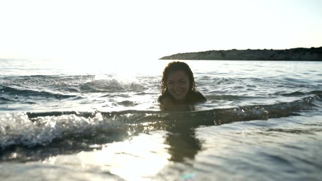 かわいい女の子が、夕日を背景に海洋の海岸でリラックスします。 - チャームポイント点の映像素材/bロール