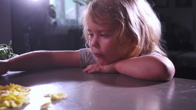 милая девушка бежит к столу на кухне и миску с кукурузными хлопьями. счастливое смешное улыбающееся детское лицо. здоровое питание для дете - голодный стоковые видео и кадры b-roll