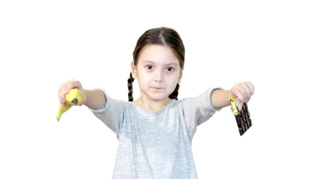 Cute girl showing banana and chocolate towards the camera