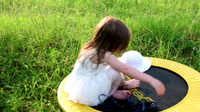 A cute girl sits in the natural garden. Little girl sits on a small trampoline. Little girl wears white wedding dress video