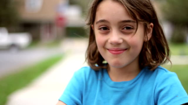 Cute Girl Smiles A young cute girl looks up and smiles to the camera. A bright and radiant face greets the audience. sideways glance stock videos & royalty-free footage