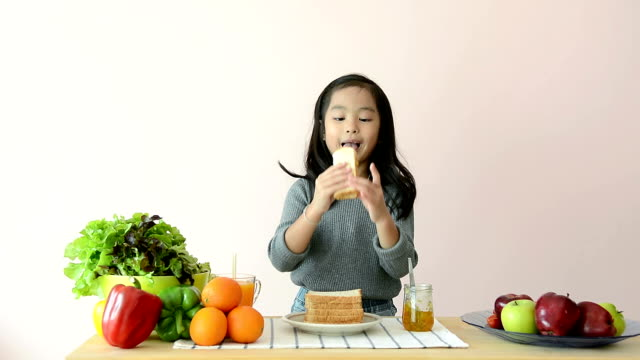 Cute Girl Spreading And Eating Jam Toast At Dining Table