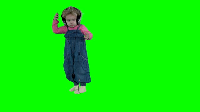 Cute girl take off huge headphones off head isolated on green background video