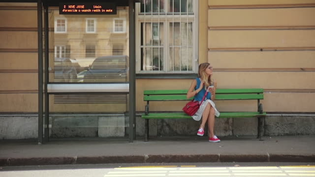 Cute girl talking on the phone and waiting for a bus in the city. Cute girl talking on the phone and waiting for a bus in the city. bus stop stock videos & royalty-free footage