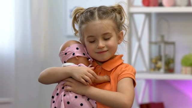 Cute girl tenderly embracing favorite baby toy, dreaming about little sister