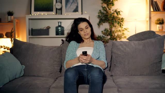 söt tjej slår på tv med fjärrkontroll tittar sitter på soffan hemma - slå på och av bildbanksvideor och videomaterial från bakom kulisserna