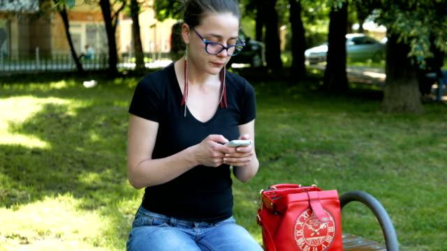 симпатичный девушка с использованием ее смартфон на свежем воздухе - google стоковые видео и кадры b-roll