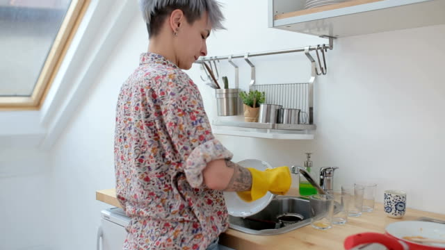 Cute girl washing dishes after breakfast Lovely woman with eyeglasses in red and white shirt, cleaning the kitchen and washing dishes after breakfast. dishwashing liquid stock videos & royalty-free footage