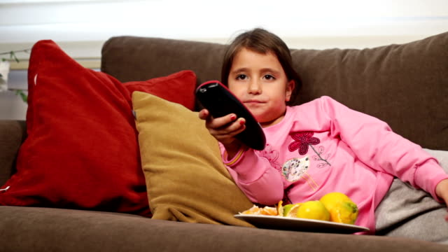 Cute girl watching television Girl change the tv channels changing channels stock videos & royalty-free footage