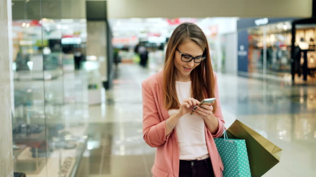 Cute girl with fair hair is using smartphone and smiling while walking in shopping mall with paper bags. Internet, modern technology and youth lifestyle concept.