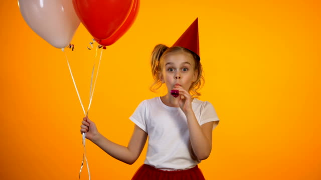 Cute girl with party blower holding air balloons and celebrating birthday, happy Cute girl with party blower holding air balloons and celebrating birthday, happy birthday background stock videos & royalty-free footage