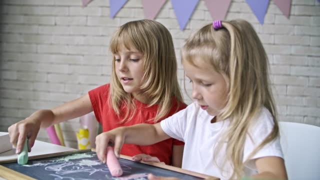 Cute Girls Drawing with Chalk on Blackboard