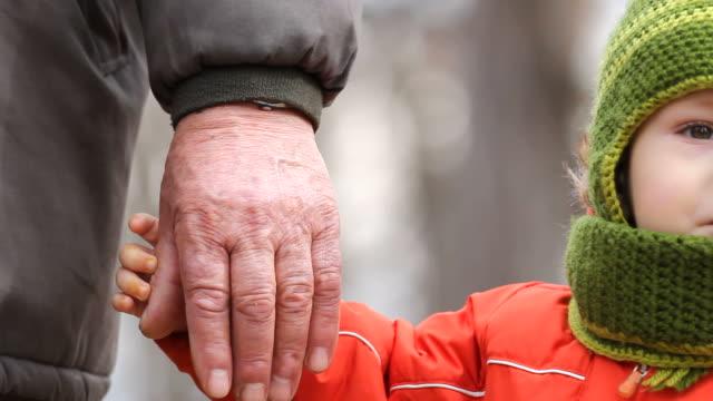 cute grandson hold grandfather hand, simple approach gesture - внук стоковые видео и кадры b-roll