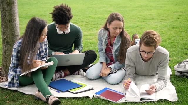 söt kille i svarta glasögon läser bok och jämför information med andra studenter - kommunikationssätt bildbanksvideor och videomaterial från bakom kulisserna