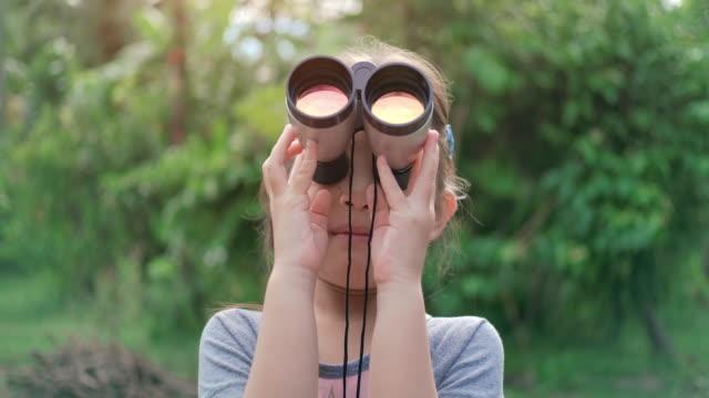 双眼鏡を使ったslo mo かわいい幸せな子供の女の子 - バードウォッチング点の映像素材/bロール