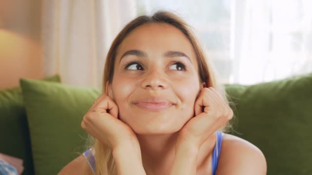 cute happy girl portrait daydreaming and falling behind on the sofa. single woman imagining and smiling at home on sofa. romantic female concept - rappresentazione umana video stock e b–roll