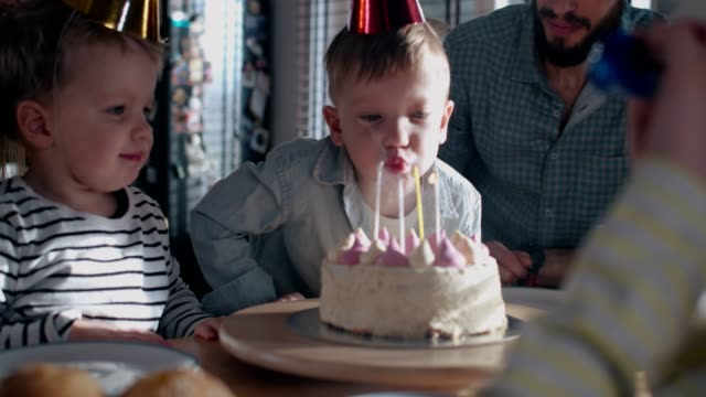 Cute happy little Caucasian boy child making wish, blowing on birthday cake at fun celebration with family slow motion.