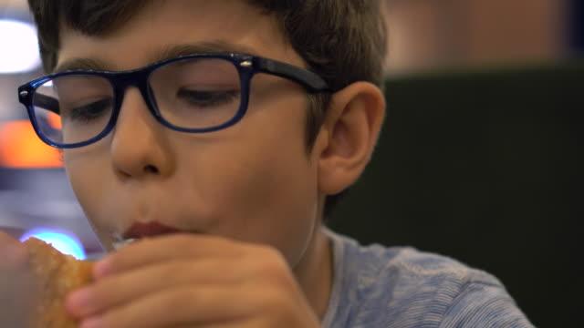 かわいい健康な男児カフェ屋外に座ってハンバーガーを食べる - 男の子点の映像素材/bロール