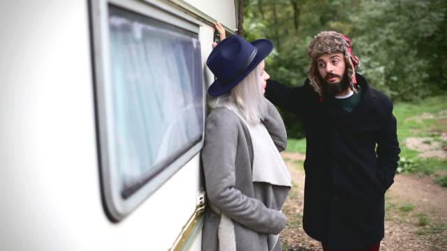 hipster bonito casal na frente de um antigo camping trailer - vídeo