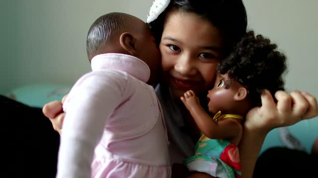 Cute hispanic little girl hugging black dolls Cute hispanic little girl hugging black dolls doll stock videos & royalty-free footage