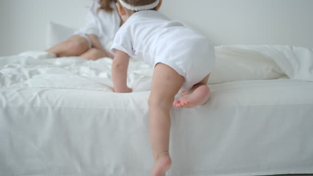 Cute Infant Baby Girl Climbing On The Bed And Crawling To Her Mom video