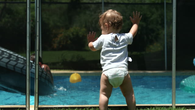 Cute infant baby leaning on swimming pool fence watching siblings play inside water
