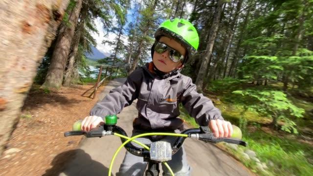 Cute Kid Cycling in the Forest around Lake Edith in Jasper, Alberta, Canada