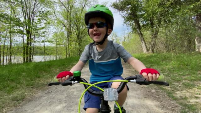 cute kid in bicicletta nella foresta con sua madre - percorso per bicicletta video stock e b–roll