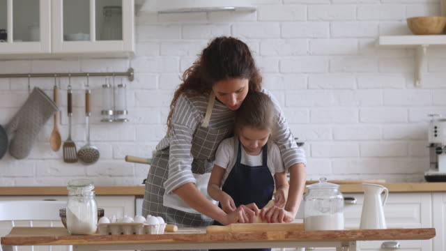 Cute kid daughter helping mom learning preparing dough in kitchen