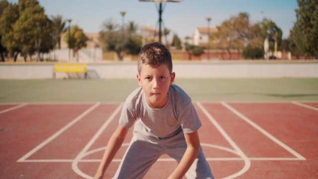 vídeos de stock e filmes b-roll de cute kid hiting a basketball ball. boy practicing shooting a basketball - desafio