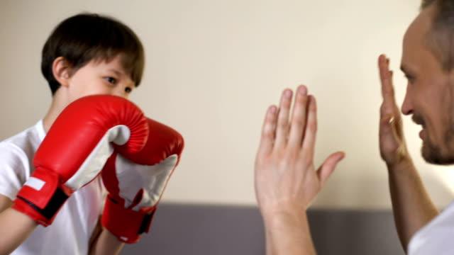 vídeos y material grabado en eventos de stock de deporte niño lindo practicando boxeo golpes con su entrenador, que se divierten con el padre, - artes marciales