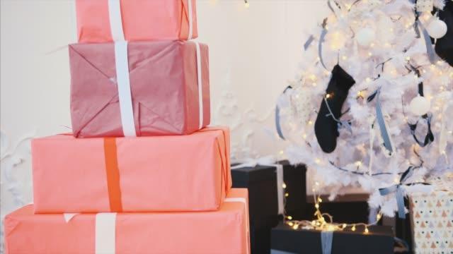 vidéos et rushes de l'enfant mignon a préparé des cadeaux de noel pour ses amis et famille et regarde dehors de derrière une pile des boîtes rouges de cadeau. - en botte ou en grappe