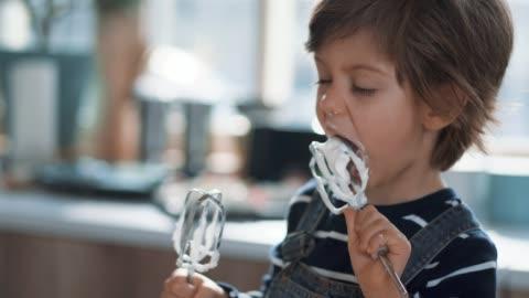 vidéos et rushes de enfant mignon dégustation chantilly crème de batteur à oeufs - manger