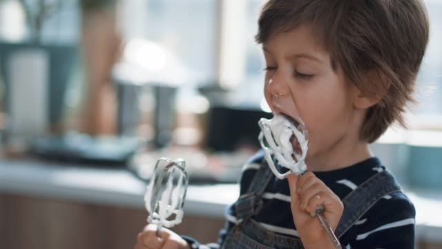 cute kid tasting whipped cream of egg beater - articoli casalinghi video stock e b–roll