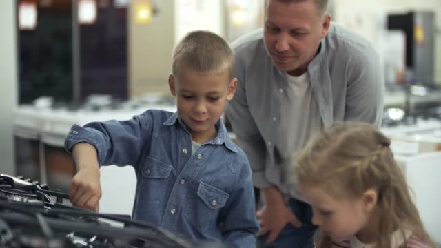 vídeos de stock e filmes b-roll de cute kids and smiling father discussing stove in home appliance store - cooker happy