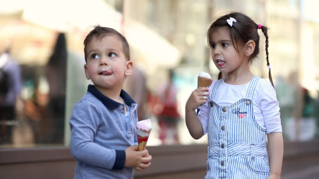 Cute Kids Sharing Ice Cream In Front Of Shopping Mall