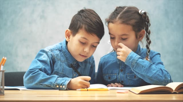 Cute kind brother is helping her sister with her homework.