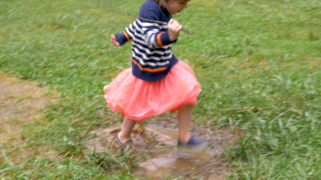 Cute little 2 year old girl running through puddle and looking at camera video
