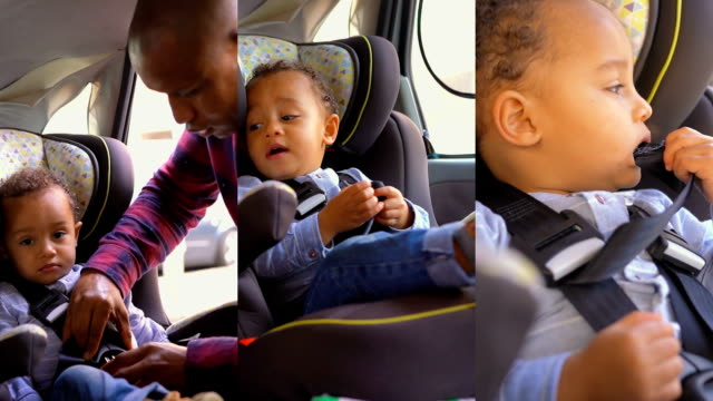Cute little African American boy sitting in child safety seat in car.