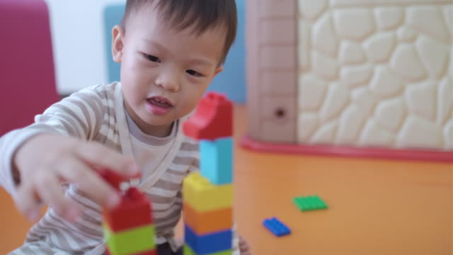 Cute little Asian 2 - 3 years old toddler boy child having fun playing with colorful plastic blocks Cute little Asian 2 - 3 years old toddler boy child having fun playing with colorful plastic blocks indoor at play school / nursery / living room, Educational toys for young children concept playroom stock videos & royalty-free footage