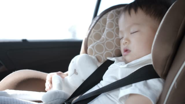cute little asian 2 - 3 years toddler baby boy child sleeping in modern car seat - 2 3 anni video stock e b–roll