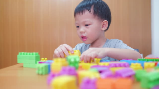 Cute little Asian 3 - 4 years old toddler boy child having fun playing with colorful plastic blocks indoor at home