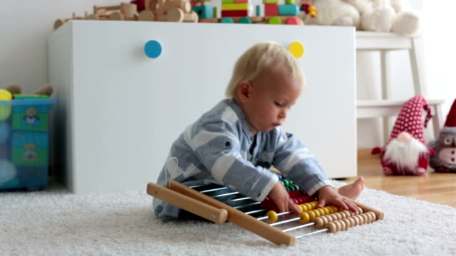 cute little baby boy, playing with abacus at home, sunny kids room - banchi scuola video stock e b–roll