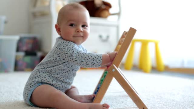 söt liten pojke, leker med abacus hemma, sunny kids room - abakus bildbanksvideor och videomaterial från bakom kulisserna