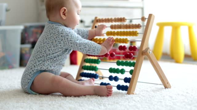 söt liten pojke, leker med abacus hemma, soliga kids rum - abakus bildbanksvideor och videomaterial från bakom kulisserna