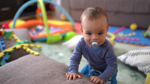 Cute little baby boy standing in his playroom near sofa bed Cute little baby boy in pajamas standing in his playroom near sofa bed playroom stock videos & royalty-free footage